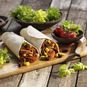 Lebensmittel perfekt in Szene gesetzt, gefüllte Wraps auf Holzbrett