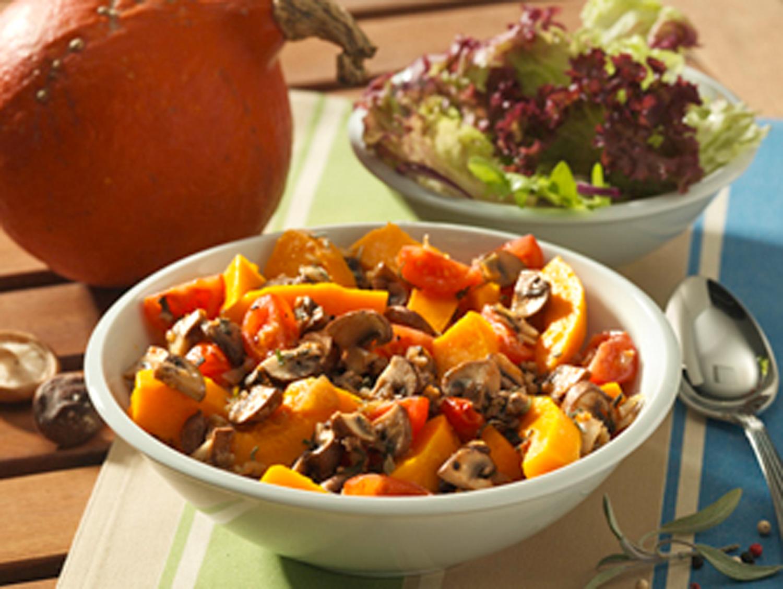 Schale mit Kürbis und Schale mit Salat auf Tisch