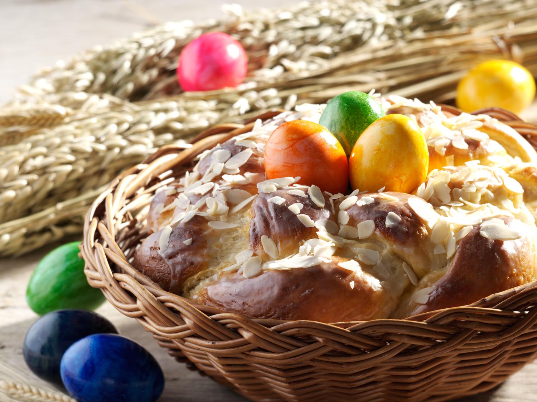 Dekorierter Korb mit Osterhefezopf und bunten Eiern