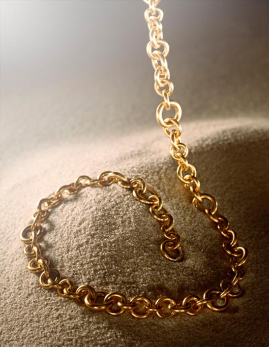 Goldkette von Niessing über feinem Sand
