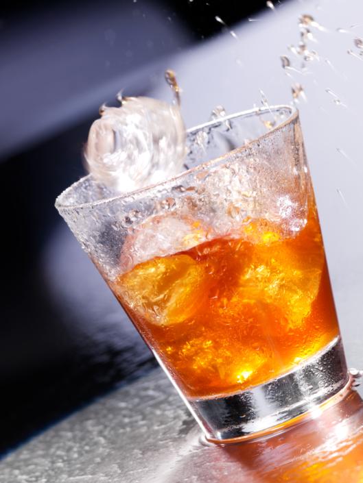 Lebensmittel perfekt in Szene gesetzt, Eiswürfel fällt in Whiskyglas