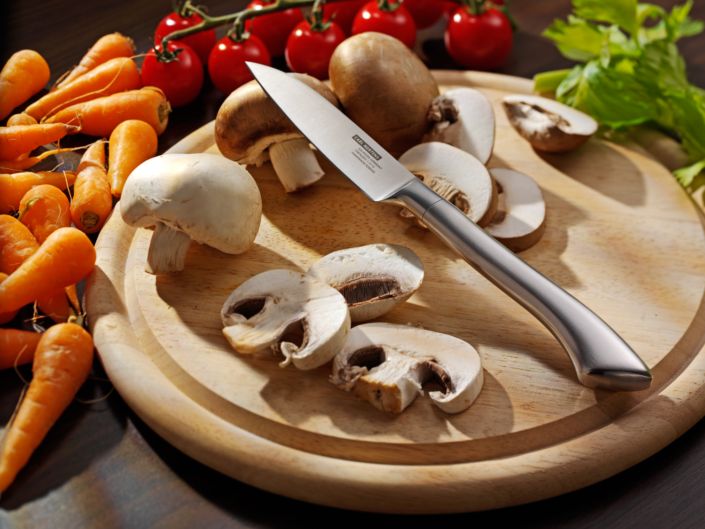 Exzellente Werbefotografie, Pilze auf Holzbrett mit Gemüsemesser