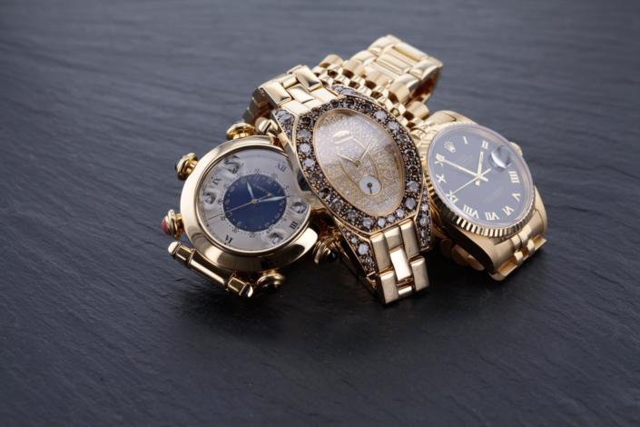 Luxusschmuck und Luxusuhren perfekt fotografiert, Drei goldene Uhren auf Schieferplatte